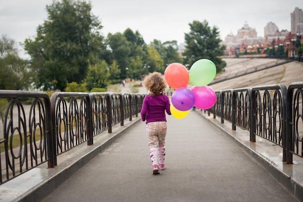 Petite fille avec des ballons dans le parc