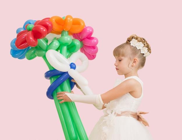 Petite fille avec des ballons dans une robe de bal isolée sur rose