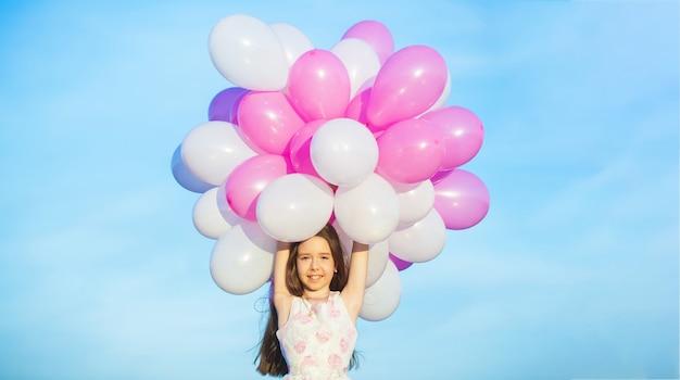 Petite fille avec des ballons. vacances d'été, célébration, enfants petite fille heureuse avec des ballons colorés.
