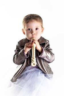 Petite fille en bas âge avec flûte sur fond blanc à la verticale.