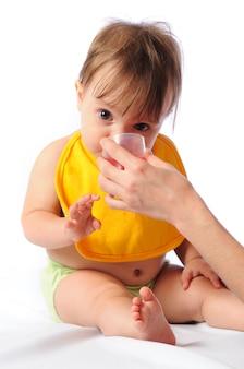 Petite fille avec bavoir regardant la caméra et eau potable ou compote de tasse.