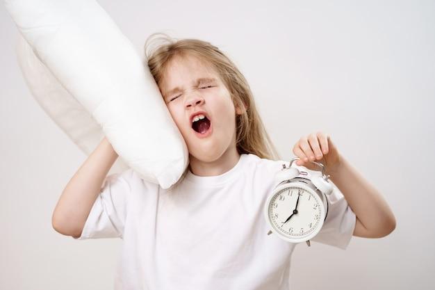 Une petite fille béante embrasse un oreiller et un réveil sur fond blanc. les premières ascensions des enfants à l'école et à la maternelle. literie confortable.