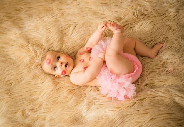 Une petite fille avec beaucoup de baisers rouges sur son corps et sa culotte rose est allongée sur une couverture beige moelleuse