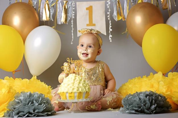 Petite fille de bébé mangeant un gâteau d'anniversaire pendant le smash party du gâteau