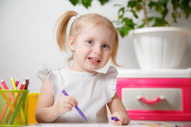 Petite fille de bébé peinture à table à la maison ou à la maternelle. adorable petit enfant mignon avec deux queues de poney dessin indoor.box avec marqueurs multicolores.