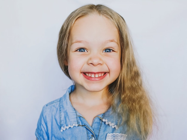 Petite fille belle bébé aux yeux bleus souriante, sur fond blanc