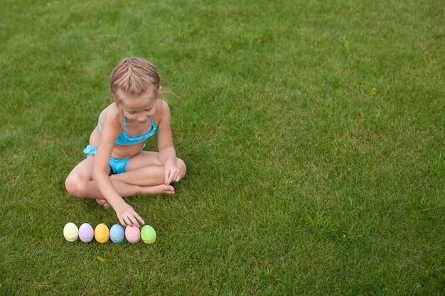 Petite fille belle considère les oeufs de pâques sur l'herbe verte