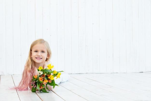 Petite fille belle enfant avec bouquet de couleurs vives sur fond de bois blanc