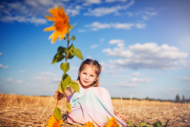 Petite fille belle joyeuse dans une longue robe d'été est assise sur un champ de blé tondu et de tournesols