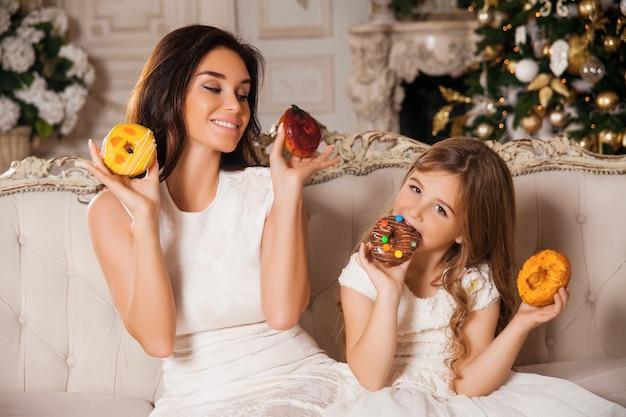 Petite fille avec une belle mère s'amusant avec des beignets