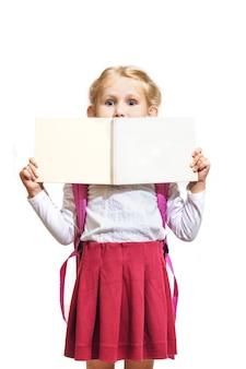 Petite fille belle et à la mode tenant un cahier vierge isolé sur fond blanc