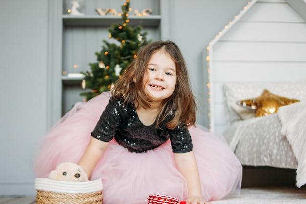 Petite fille en belle robe avec jouet pour chien dans la chambre