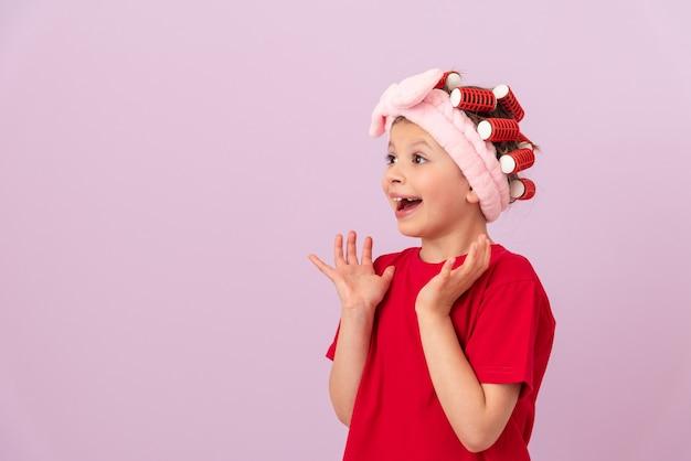 Une petite fille avec des bigoudis sur la tête est heureuse.