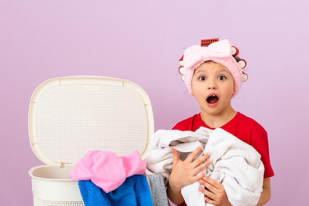 Une petite fille avec des bigoudis va laver le linge sale.