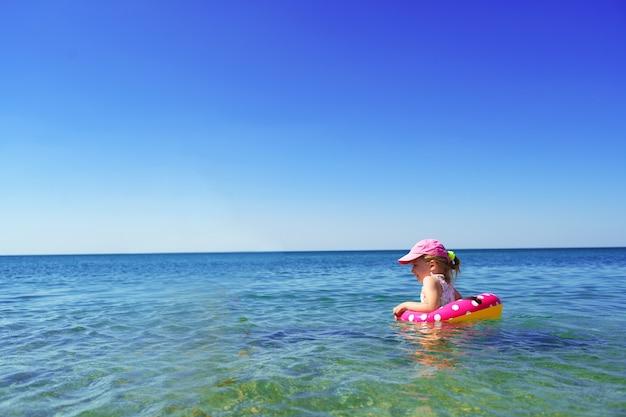 Petite fille en bikini nageant en mer avec cercle de natation seul