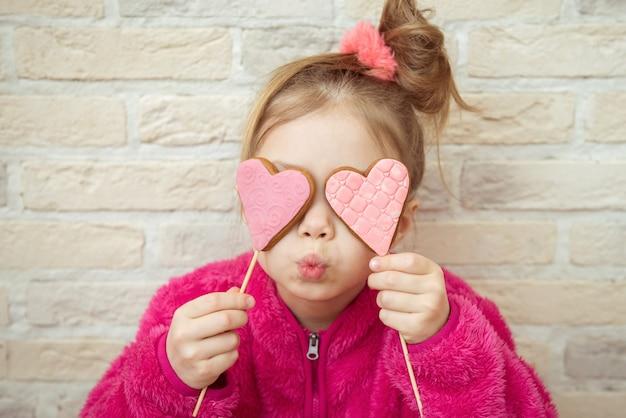 Petite fille avec des biscuits en forme de coeur valentine dans ses mains. concept d'amour