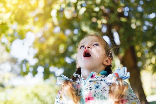Une petite fille blanche heureuse avec deux nattes dans une veste multicolore surprise que l'automne soit venu et qu'il est temps d'aller à l'école par une chaude journée d'automne