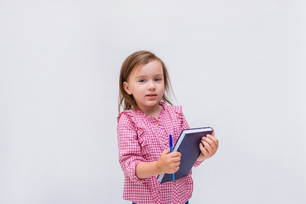 Une petite fille avec un bloc-notes et un stylo dans une chemise à carreaux sur un blanc isolé