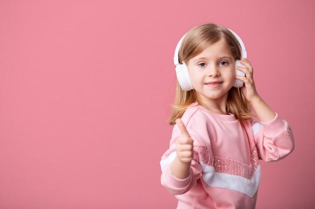 Une petite fille blogueuse écoute de la musique dans des écouteurs blancs