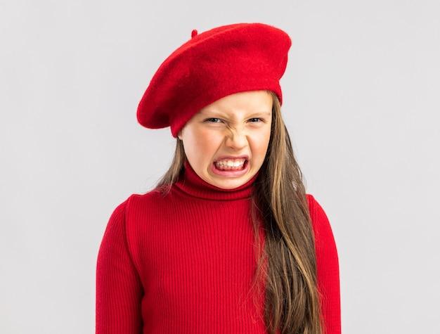 Petite fille blonde agacée portant un béret rouge isolé sur un mur blanc avec espace de copie
