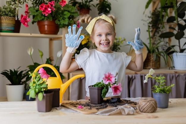 Petite fille blonde d'apparence européenne avec un arc sur la tête et portant des gants de travail plantes fleurs
