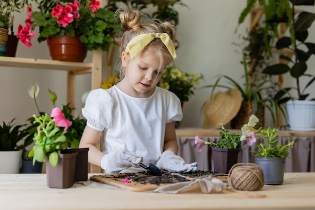 Petite fille blonde avec un arc sur la tête plantes et greffes et arrose les fleurs d'intérieur