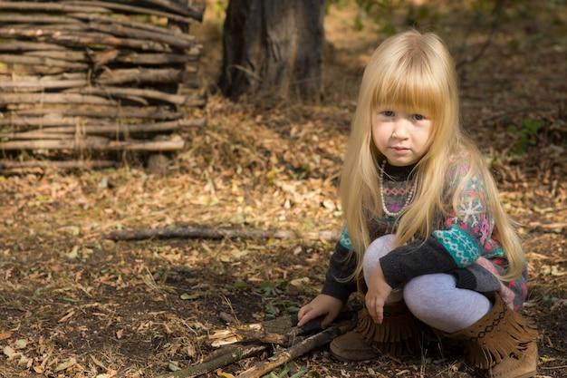 Petite fille blonde assez sérieuse jouant dehors dans le jardin avec des brindilles en bois accroupies sur le sol devant une clôture en bois rustique