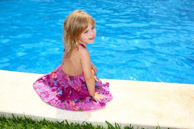 Petite fille blonde assise souriant piscine