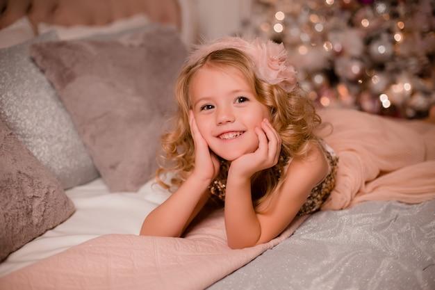 Petite fille blonde au lit à côté de l'arbre de noël. réveillon de noël