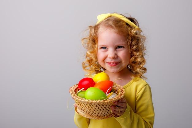 Une petite fille blonde aux cheveux bouclés souriant tenant un panier d'oeufs de pâques sur un espace blanc