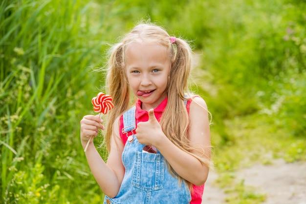 Petite fille blonde aux cheveux longs et bonbons sur un bâton