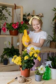 Petite fille blonde avec bandeau sur la tête et portant des gants de travail sprays ou eau fleurs d'intérieur