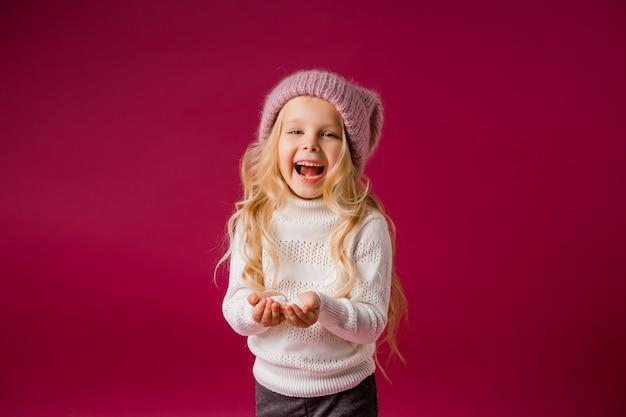 Petite fille blonde avec un bonnet tricoté et un pull joue avec la neige