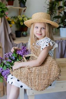 Petite fille blonde avec un bouquet de fleurs lilas est assise sur une chaise en bois dans le style de vie de la chambre