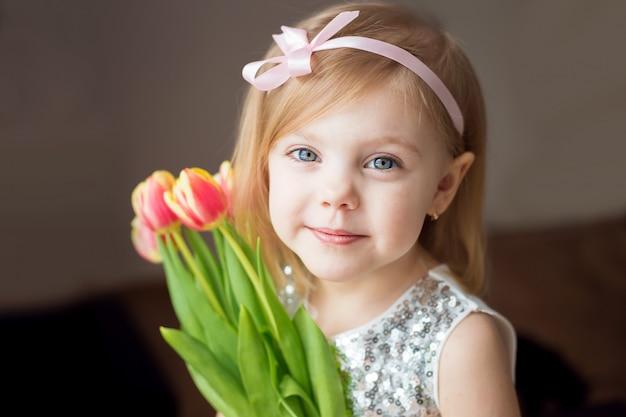 Petite fille blonde avec un bouquet de tulipes., pressée aux couleurs d'une robe blanche avec un ruban dans les cheveux, image horizontale, avec un sourire joyeux