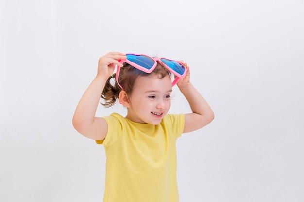 Une petite fille blonde brandit de grosses lunettes drôles sur un espace blanc. journée de rire. jeu pour enfants.