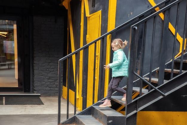 Petite fille blonde caucasienne dans des vêtements à la mode descend les marches en métal de la salle d'exposition de vêtements dans un centre urbain élégant