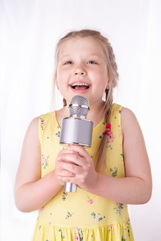 Une petite fille blonde chante une chanson dans un microphone dans ses mains