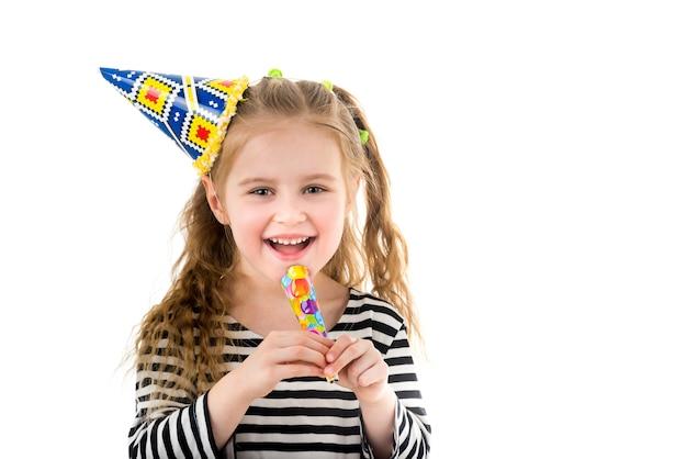Petite fille blonde en chapeau de fête coloré à l'aide d'un souffleur de fête