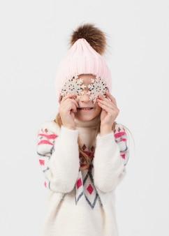 Petite fille blonde couvrant son visage avec des flocons de neige