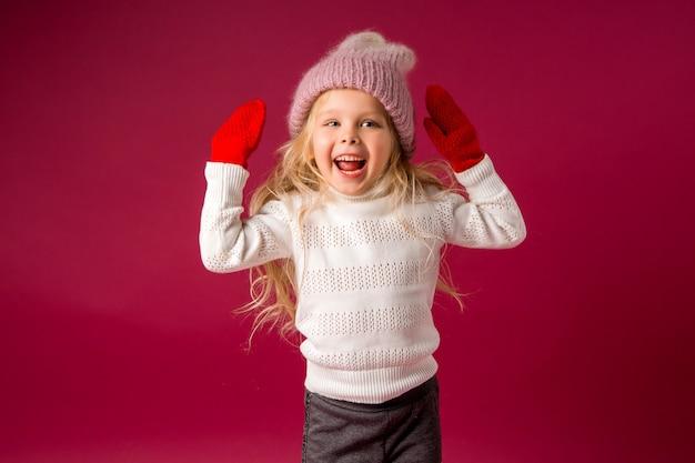 Petite fille blonde dans un bonnet tricoté et des mitaines sourit. vêtements d'hiver