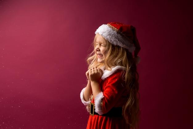 Petite fille blonde dans un costume de père noël fait un vœu
