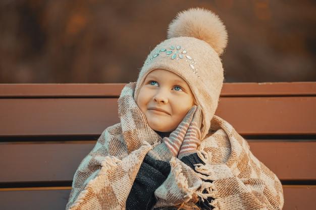 Petite fille blonde dans un plaid dans le parc sur un banc