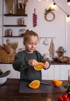 Une petite fille blonde dans un pull vert est assise à la table et mange une orange