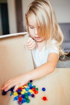 Petite fille blonde dans un t-shirt blanc jouant avec une mosaïque multicolore en plastique à la maison ou au préscolaire. concept d'éducation précoce.