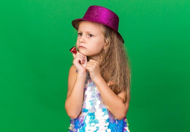 Petite fille blonde désemparée avec un chapeau de fête violet tenant un sifflet de fête et regardant le côté isolé sur un mur vert avec espace de copie