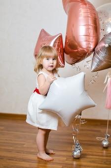 Petite fille blonde de deux ans avec de gros ballons roses et blancs pour sa fête d'anniversaire.