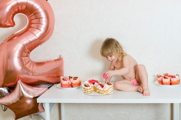 Petite fille blonde de deux ans mange un gâteau