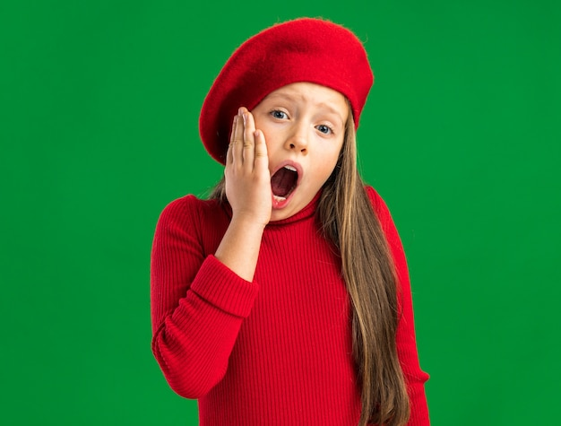 Petite fille blonde douloureuse portant un béret rouge regardant à l'avant en gardant la main sur le menton avec la bouche ouverte isolée sur un mur vert avec espace pour copie