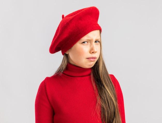 Petite fille blonde douteuse portant un béret rouge isolé sur un mur blanc avec espace pour copie